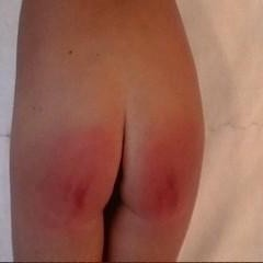 "Carissa with her nose to the wall and red bottom on display after 3 spankings in ""Model Problem"""